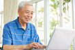 Senior Chinese Man Sitting At Desk Using Laptop At Home