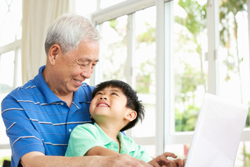 Chinese Grandfather And Grandson Sitting At Desk Using Laptop