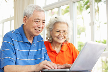 Senior Chinese Couple Sitting At Desk Using Laptop At Home
