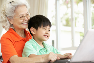 Chinese Grandmother And Grandson Sitting At Desk Using Laptop