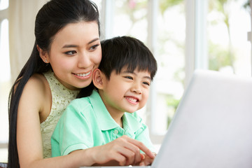 Chinese Mother And Son Sitting At Desk Using Laptop At Home