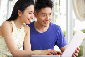 Young Chinese Couple Sitting At Desk And Using Laptop At Home