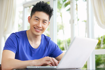 Young Chinese Man Sitting At Desk Using Laptop At Home