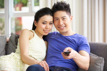 Young Chinese Couple Sitting And Watching TV On Sofa At Home