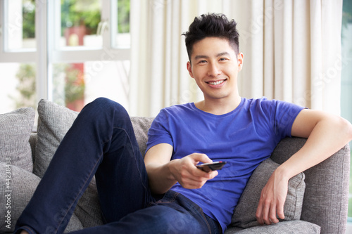 Young Chinese Man Sitting And Watching TV On Sofa At Home