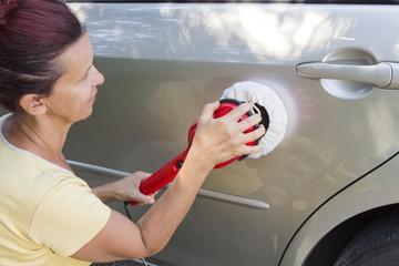 Mid aged cute woman polishing car