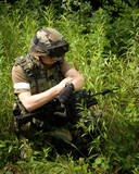 Soldier on the war in sunny day with gun in green bushes check t
