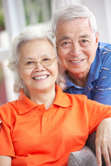 Senior Chinese Couple Relaxing On Sofa At Home