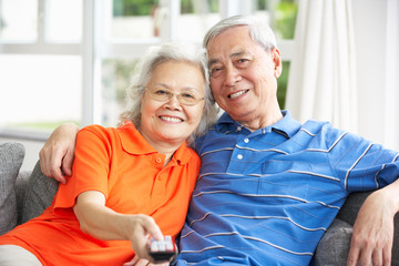 Senior Chinese Couple Watching TV On Sofa At Home