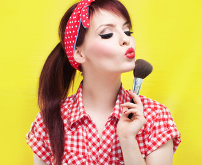 Pin up girl applying blusher