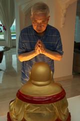 Senior Chinese Man Praying To Statue Of Buddha At Home
