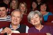 Senior Couple Watching Film In Cinema