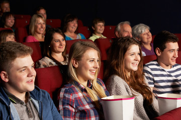 Group Of Teenage Friends Watching Film In Cinema