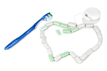 Chewing gum, dental floss and toothbrush isolated on white
