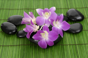 Set of beautiful orchid and zen stone on bamboo stick straw mat