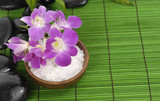 herbal salt in bowl with orchid and stones on green mat
