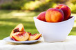 Sliced peach and bowl full of peaches