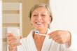 Senior woman hold toothbrush and glass water
