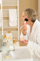 Senior woman apply make-up powder in bathroom
