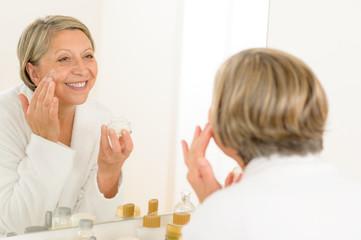 Mature woman apply cream looking bathroom mirror