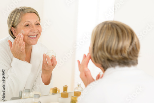 Mature woman apply cream looking bathroom mirror