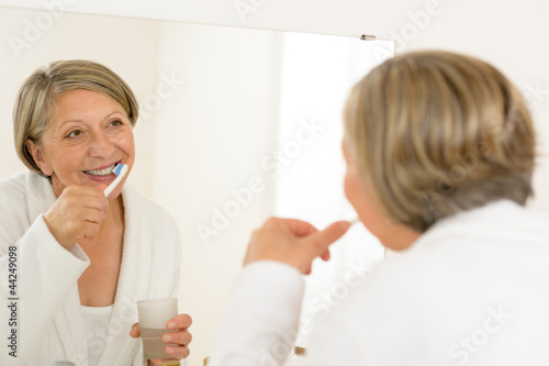 Mature woman brushing teeth look bathroom mirror