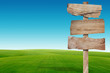 road sign with green grass and blue sky