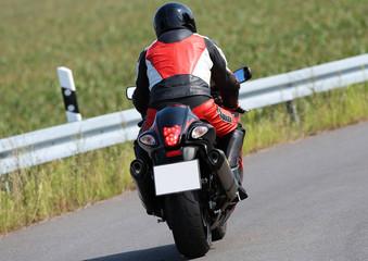 Motorradfahrer von hinten mit leerem Nummernschild
