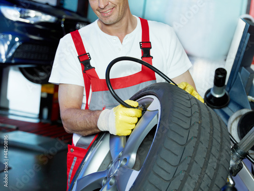 Master mechanic in a garage is checking tyre pressure
