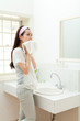 Beautiful young woman washing face