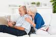 lachendes senioren-paar schaut auf tablet