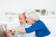 lachendes senioren-paar zeigt auf tablet