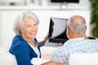 glückliches senior-paar hält laptop in der hand