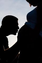 Contraluz de beso a embarazada
