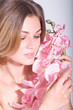 Beauty face of the young woman with pink orchid on background