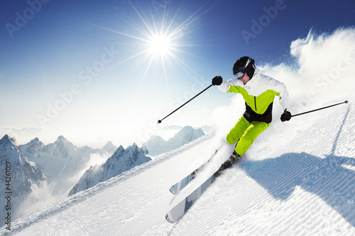 Foto op Canvas Wintersporten Skier in mountains, prepared piste and sunny day