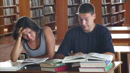 tired students in the library reading books 3