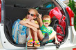 a little girl  and boy sitting in the car with backpacks