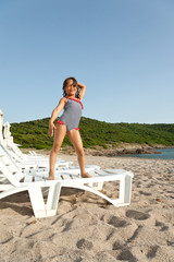 young girl standing on chairs in vacation
