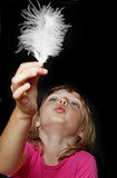 little girl blowing into white feather on black background