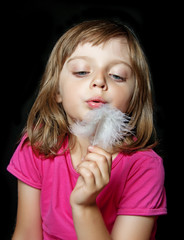little girl blowing white feather on black background