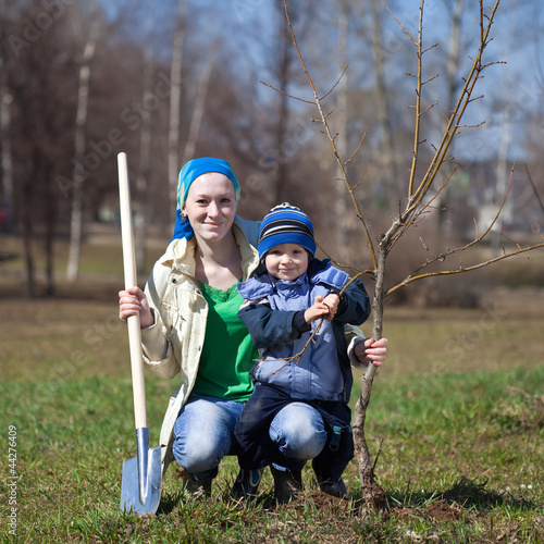 woman with her son planting  tree outdoor