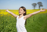 Little girl in front of canola field relaxing