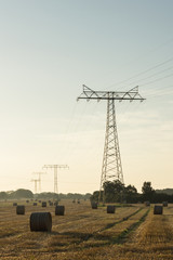 Energienetz auf Feld mit Strohballen im Morgenlicht