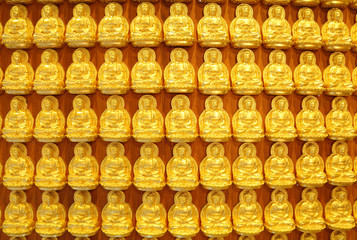 The beautiful small golden Buddha on the wall.