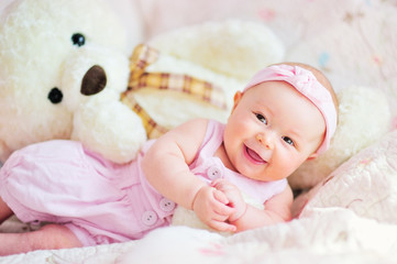 pretty smiling baby girl and teddy bear at the bed