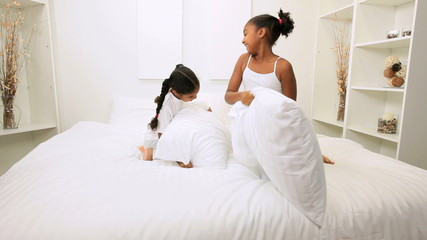 Little ethnic girls play pillow fight bedroom