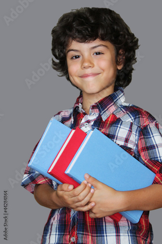 A charming boy with curly hair is holding books, isolated