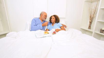 Ethnic Seniors Sharing Breakfast Bed