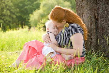 Happy mother and baby with Down syndrome hugging and kissing